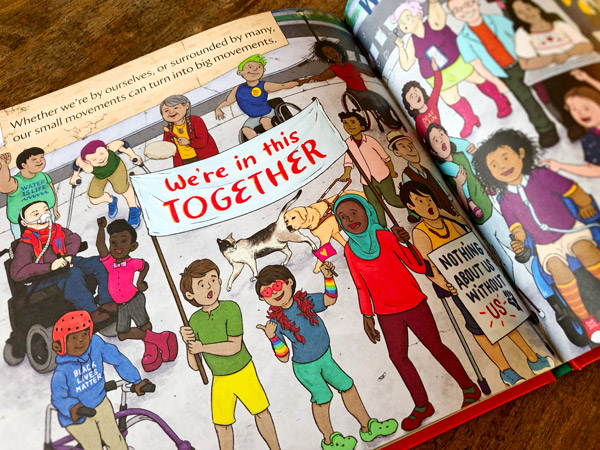 Close-up of We Move Together's spread, where several characters are seen in a march holding up protest signs and placards